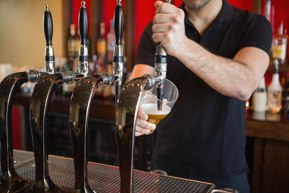 Barkeeper pulling a pint of beer behind the bar.jpeg
