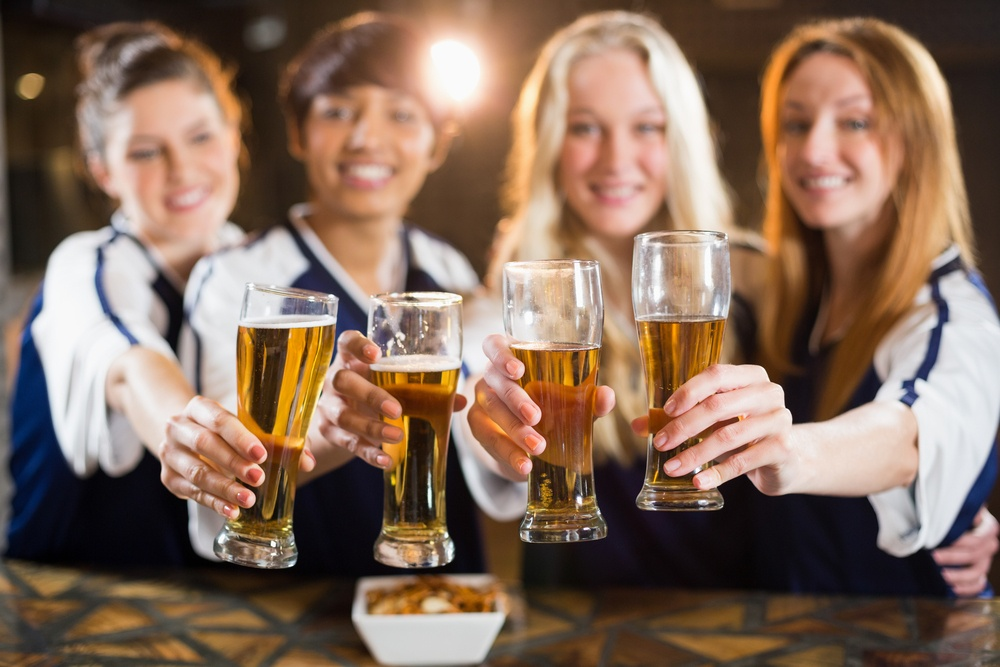 Portrait of smiling friends holding glass of beer in party at bar.jpeg