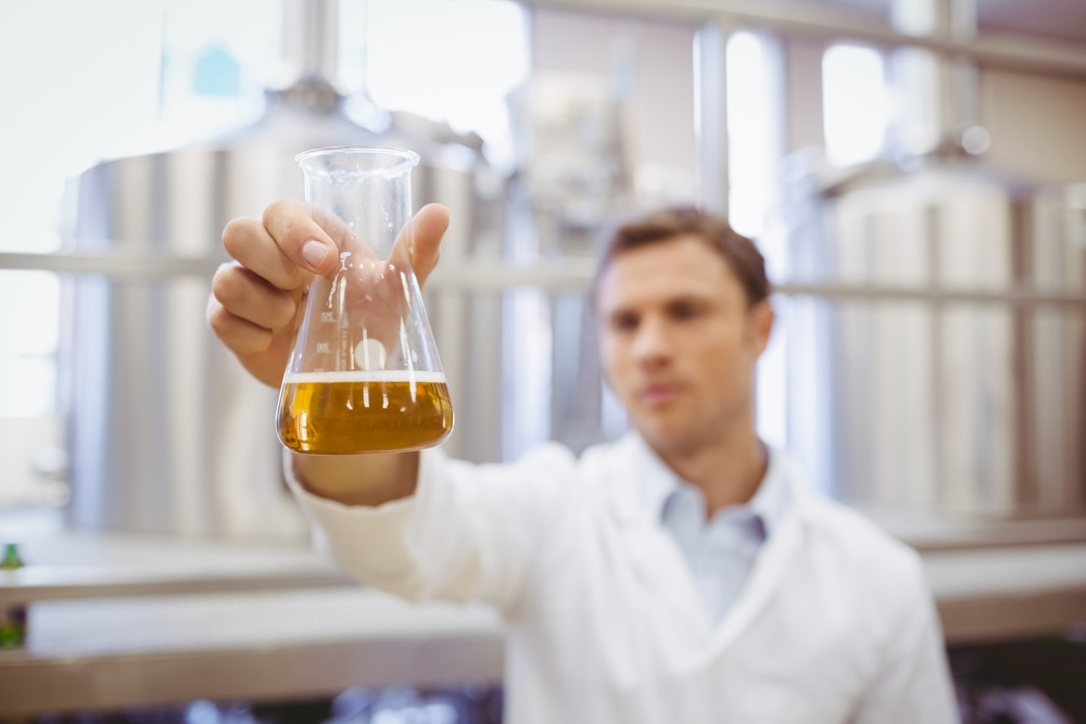 Thoughtful scientist holding a beaker in the factory.jpeg