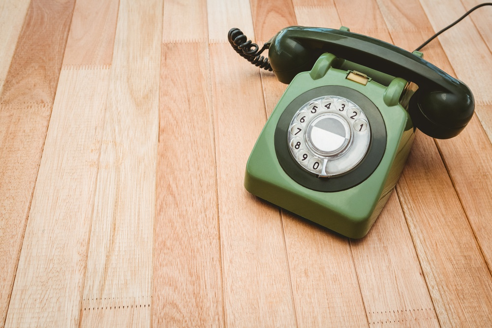 View of an old phone on wood desk.jpeg